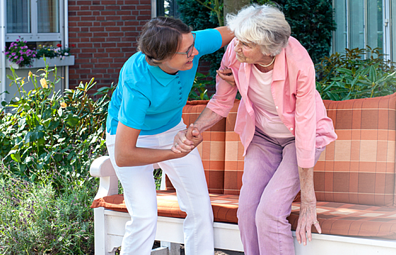 A caregiver assisting an elderly in standing up