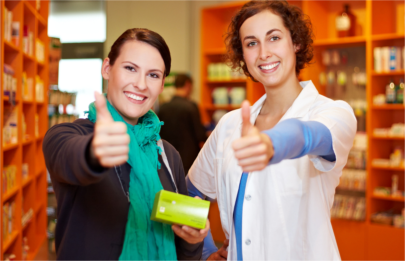 A pharmacist and a customer doing a thumbs-up sign